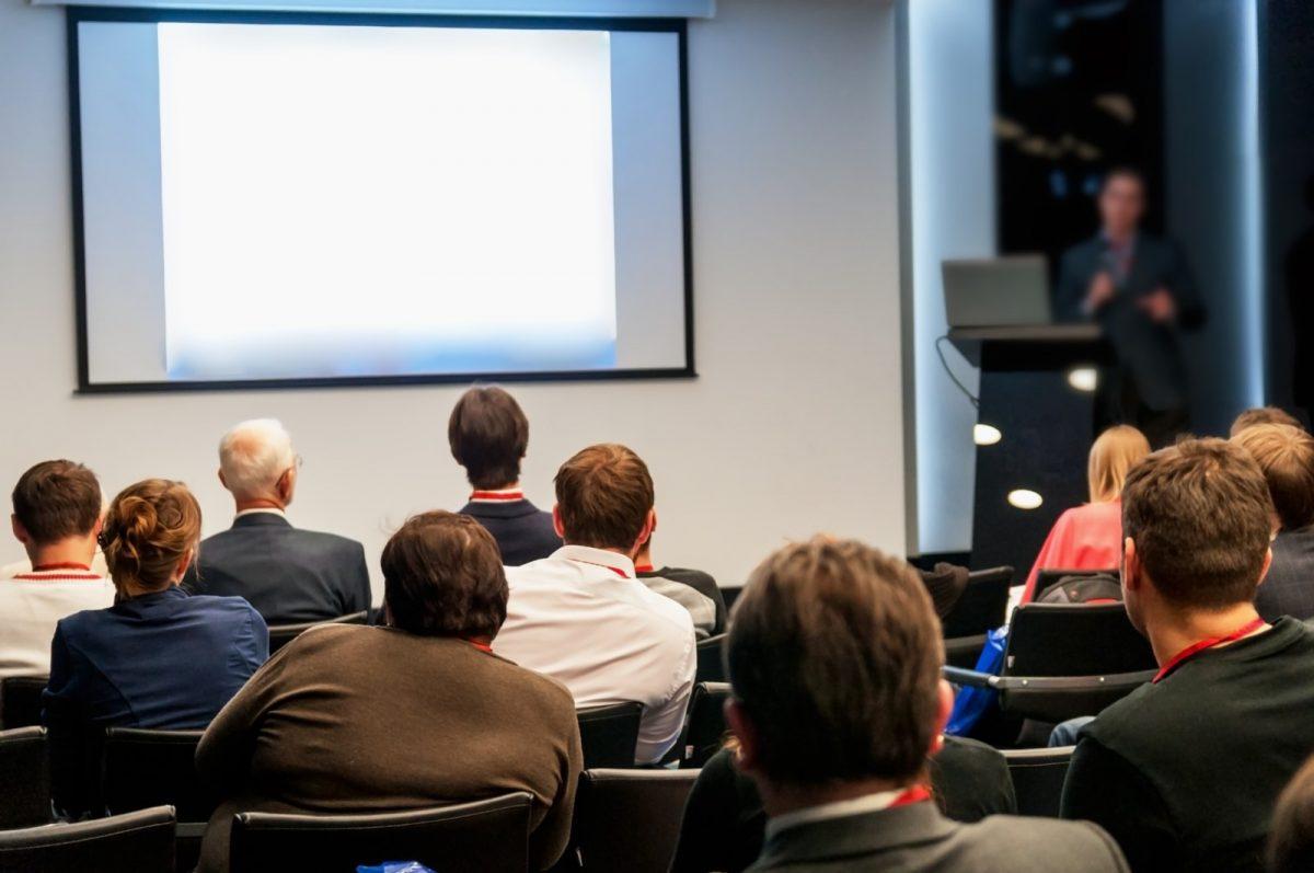 Orador con audiencia y pantalla